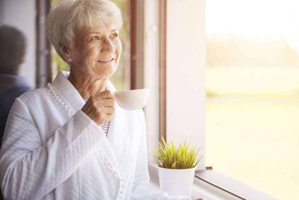 Smiling senior woman in robe holding coffee looking out window in the morning