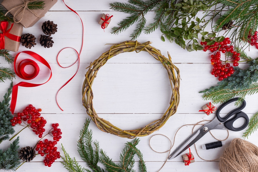 Twig wreath on table surrounded by scissors, ribbon, pine branches, berries, pinecones, etc