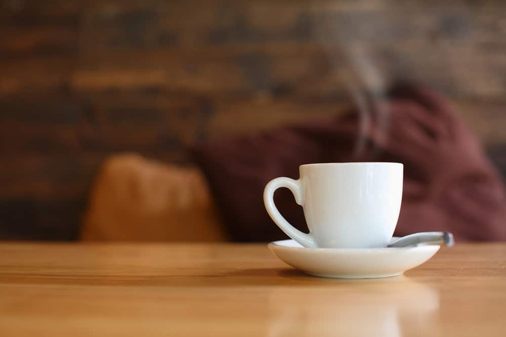 steaming cup of coffee on wooden table