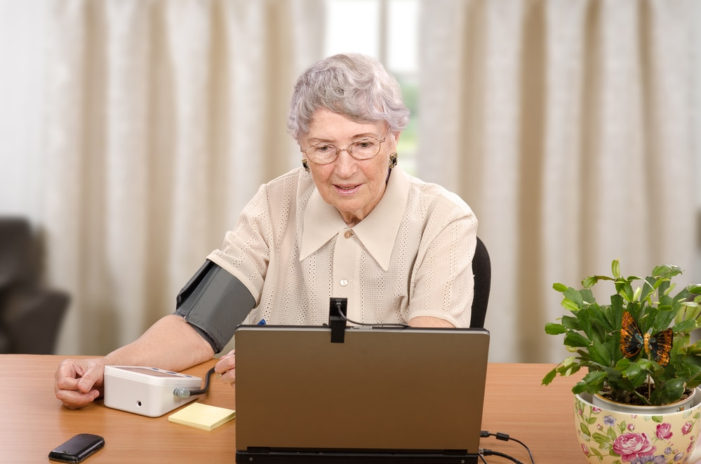 Senior woman checking blood pressure and talking to telemedicine doctor with laptop