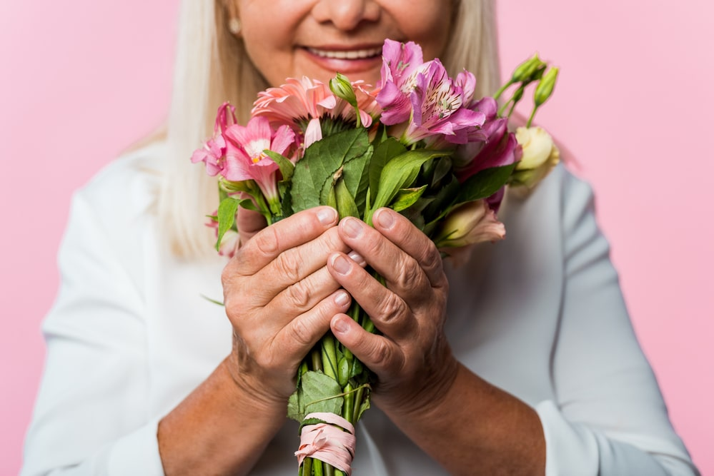 Close-up of smiling senior woman holding pink bouquet of flowers