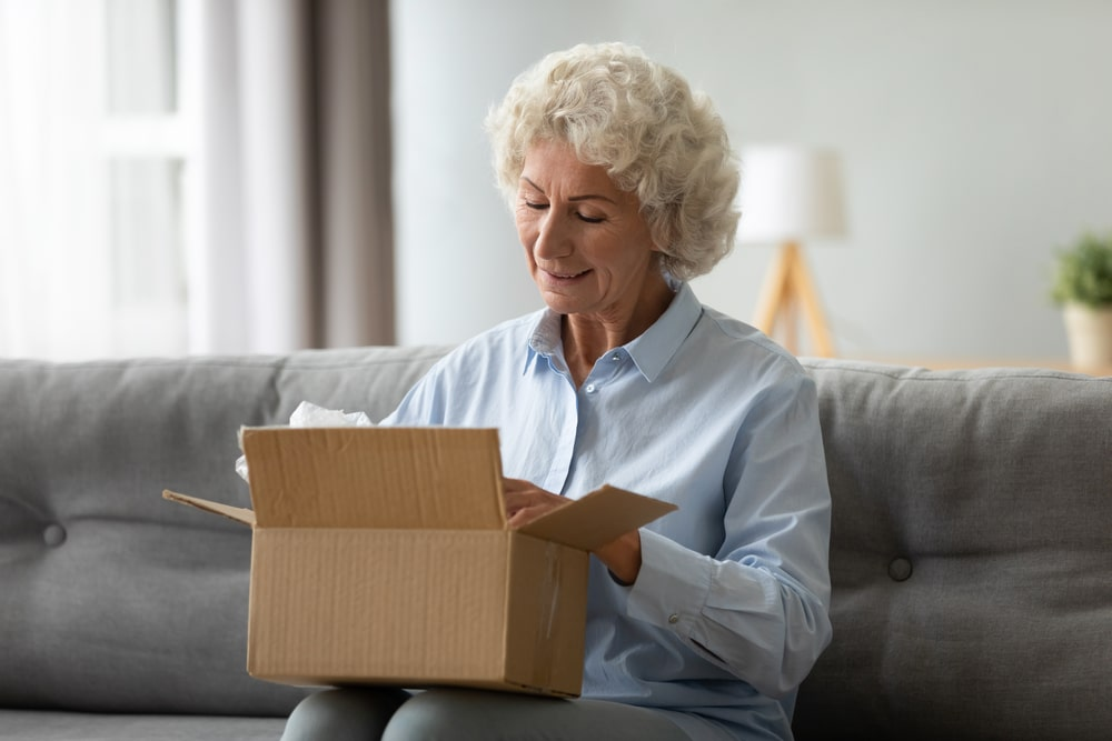 Senior woman opening package on couch