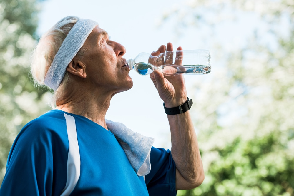 Senior man in athletic clothing drinking from water bottle outside
