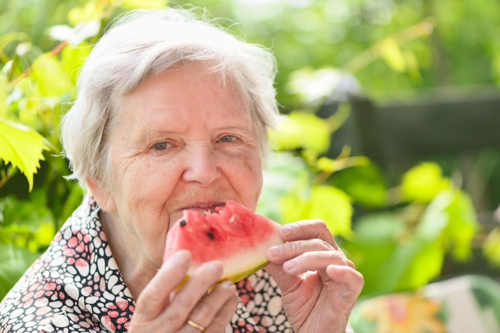 Senior woman smiling and eating watermelon outside
