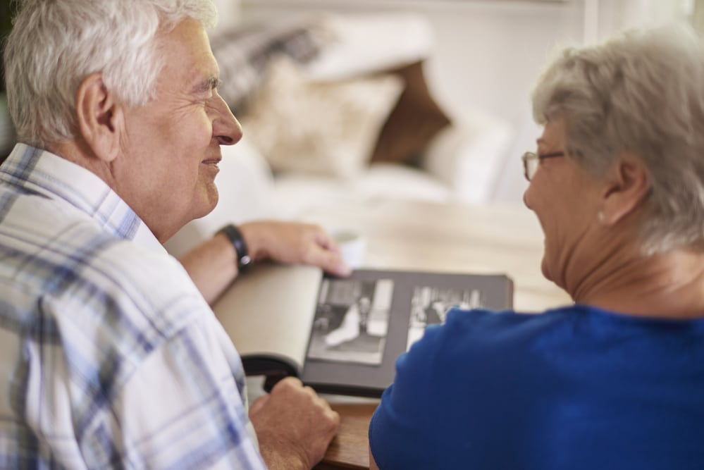 Smiling senior couple looking at photo album together