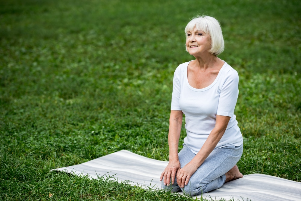 Senior woman kneeling on mat outside, looking calm and peaceful